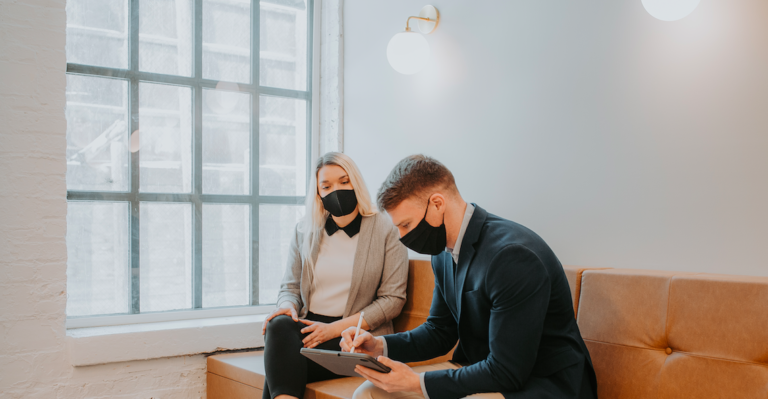 Two business professionals in masks collaborating on a project on an iPad.