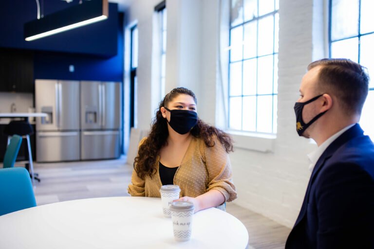 Young woman wearing a mask conversing in a breakroom with a man also wearing a black mask.