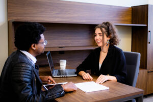Business professional man and woman meeting in an office discussing papers.
