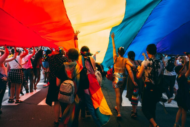 Group of parade participants marching under the gay pride flag. Photo provided by Unsplash.