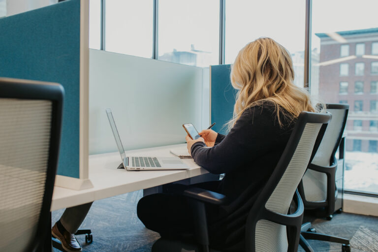 Photo from the back of a woman sitting in a coworking space. She's at her desk looking at her phone while the laptop is on the desk.